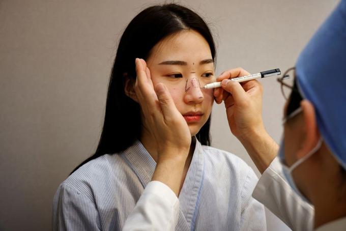 Bác sĩ tạo dáng mũi trước khi phẫu thuật cho một bệnh nhân tại bệnh viện thẩm mỹ ở Seoul, Hàn Quốc, hồi tháng 12/2020. Ảnh: Reuters.
