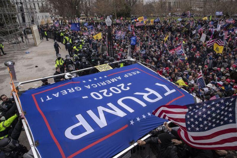 Nhóm bạo loạn tại tòa nhà Quốc hội mang theo banner ủng hộ ông Trump hôm 6/1. Ảnh: Bloomberg.