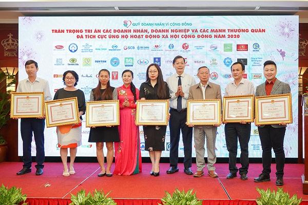 Bà Phan Kiều Thanh Hương - Phó Chủ tịch Ủy ban MTTQ Việt Nam TP.HCM (áo dài) trao bằng khen các doanh nghiệp đã tích cực tham gia các hoạt động xã hội - từ thiện năm 2020