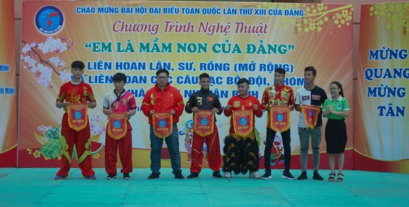 Đồng chí Nguyễn Thuận An (bên phải) – Phó bí thư quận đoàn, giám đốc nhà thiếu nhi trao cờ lưu niệm cho các đoàn lân