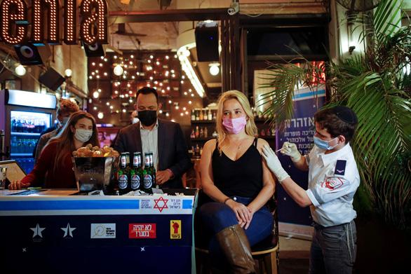 Một nhân viên y tế ở Tel Aviv, Israel tiêm vắc xin ngừa COVID-19 cho người dân ngày 18-2. Tất cả người đến tiêm được quán bar địa phương mời nước uống miễn phí - Ảnh: REUTERS