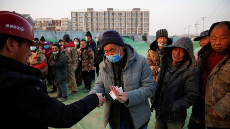 Một công nhân chính trả lương cho người lao động bằng tiền mặt tại một công trường xây dựng ở Bắc Kinh vào ngày 5 tháng 2. Ảnh: Reuters