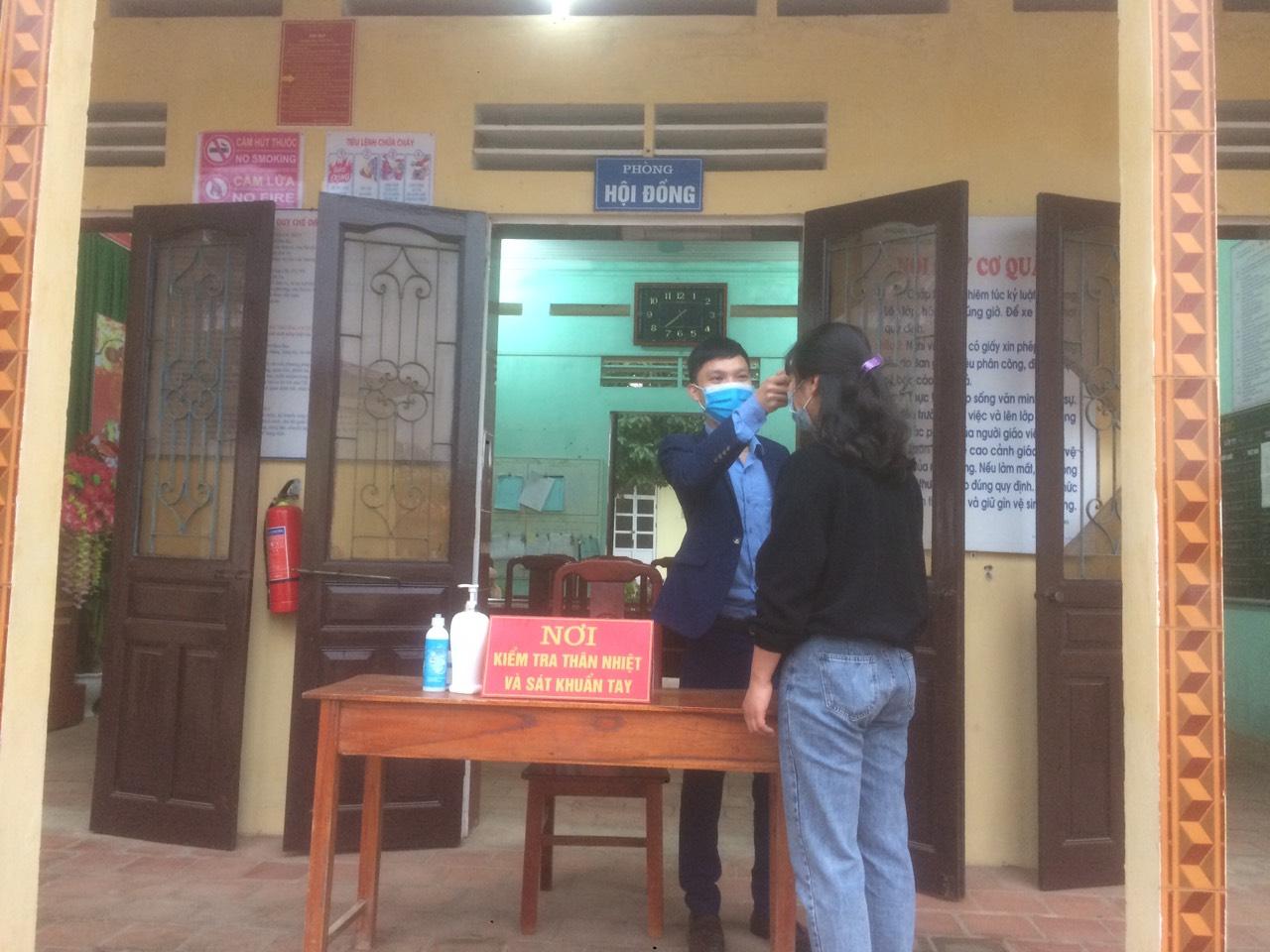 Các học sinh trường Mầm non Minh côi, xã Minh Côi, huyện Hạ Hòa được các cô giáo đo thân nhiệt ngay từ ngoài cổng trường