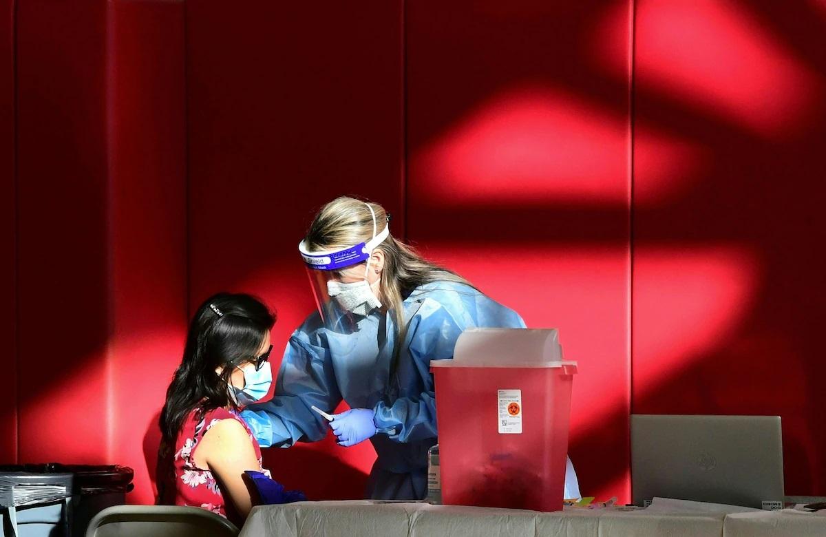 Một y tá đã đăng ký tiêm vắc-xin COVID-19 vào cánh tay của một phụ nữ tại phòng tập thể dục của Trường Trung học Corona ở thành phố Corona, miền Nam California vào ngày 15 tháng 1