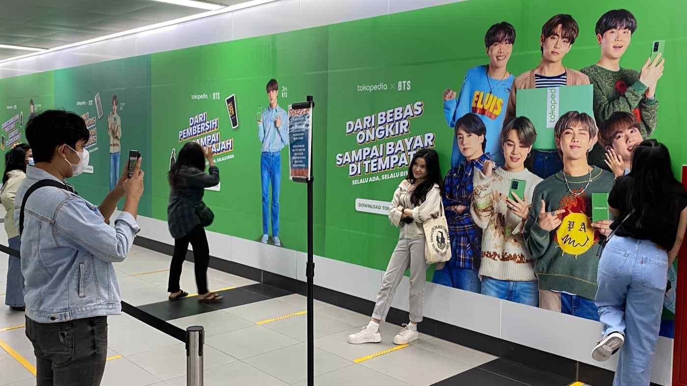 Một người phụ nữ đứng trước quảng cáo của công ty thương mại điện tử Indonesia Tokopedia có nhóm nhạc nam Hàn Quốc BTS tại một ga tàu điện ngầm ở Jakarta.