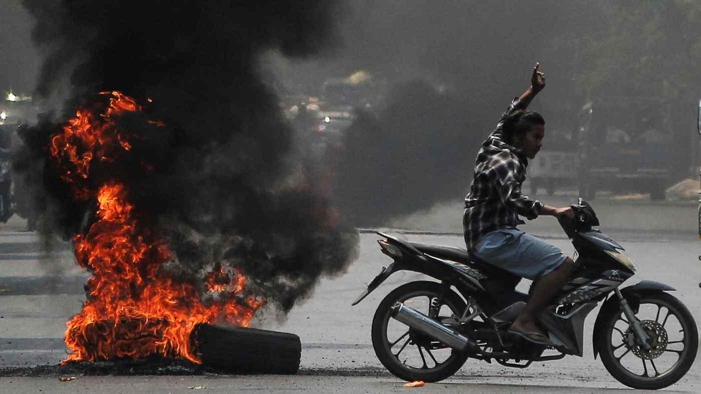 Một người đàn ông giơ ba ngón tay chào khi đi ngang qua những chiếc lốp xe đang bốc cháy trong cuộc biểu tình phản đối cuộc đảo chính quân sự ở Mandalay. © Reuters