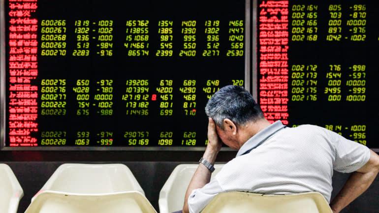 Một nhà đầu tư phản ứng khi theo dõi bảng điện tử tại một công ty môi giới chứng khoán ở Bắc Kinh vào ngày 24 tháng 8 năm 2015, sau khi chỉ số chứng khoán Shanghai Composite điểm chuẩn giảm hơn 7% do lo ngại về sự suy thoái ở Trung Quốc. © EPA / Jiji.