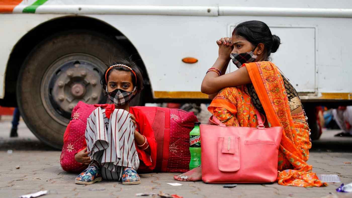 Gia đình một công nhân nhập cư ngồi cạnh xe buýt tại một bến xe buýt, khi họ chờ đợi để trở về làng của mình, sau khi chính quyền Delhi ra lệnh khóa cửa sáu ngày. © Reuters