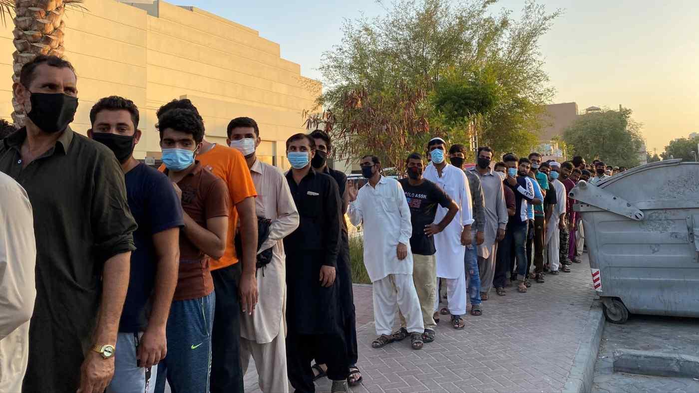 Những người đàn ông thất nghiệp xếp hàng ở Dubai để được phát thực phẩm sau khi bị mất việc làm vào năm ngoái trong đại dịch COVID-19. © Reuters