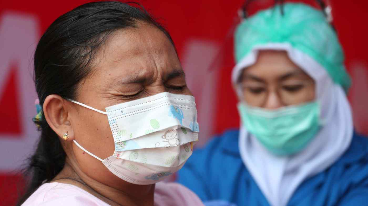 Một phụ nữ được tiêm vắc-xin COVID ở Jakarta vào ngày 10 tháng 6: Nếu không có thêm vắc-xin, Đông Nam Á sẽ không thể vượt qua giai đoạn cấp tính của đại dịch. © AP