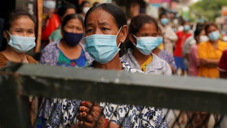 Dân làng đứng sau hàng rào ngăn chặn để yêu cầu quyên góp thực phẩm ở Phnom Penh vào ngày 30 tháng Tư: phụ nữ đã bị ảnh hưởng một cách tương xứng. © Reuters