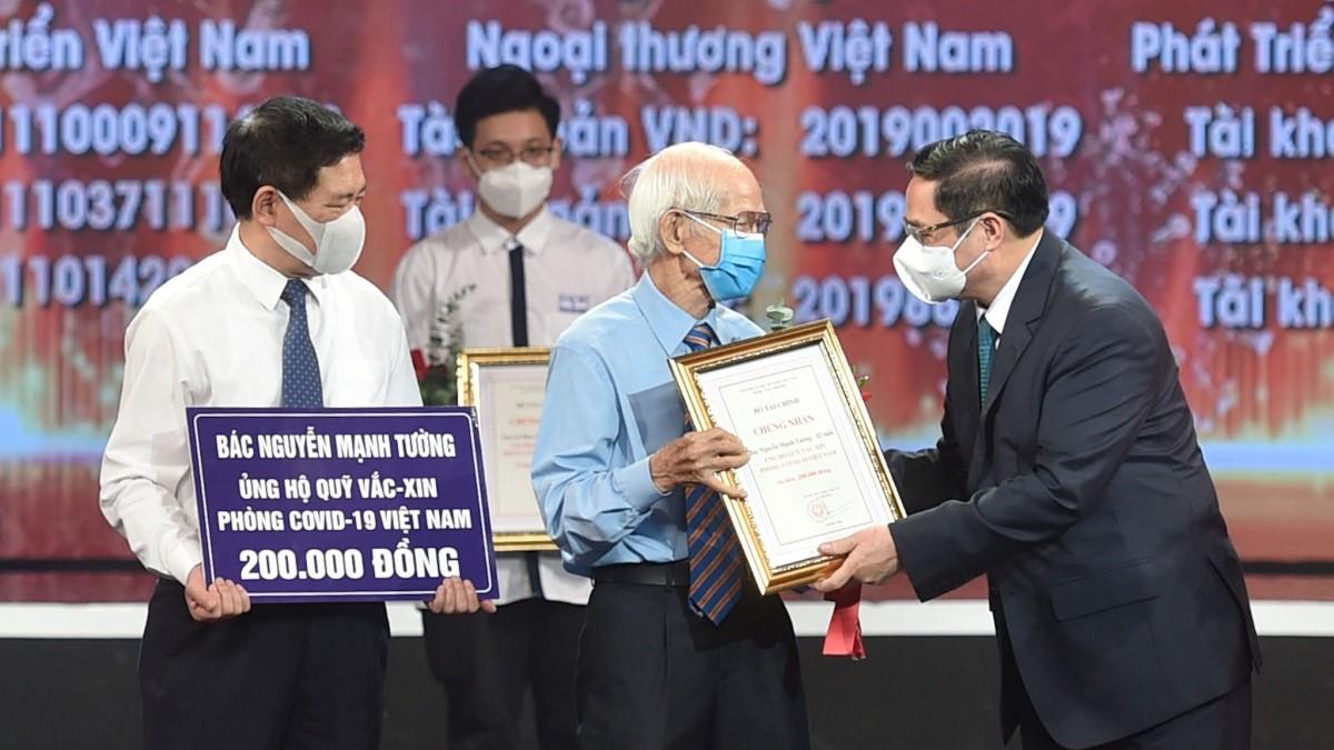 Thủ tướng Chính phủ Phạm Minh Chính trao chứng nhận, hoa cảm ơn bác Nguyễn Mạnh Tường, 82 tuổi, cán bộ hưu trí ngành đường sắt tại lễ ra mắt Quỹ vaccine phòng, chống Covid-19.