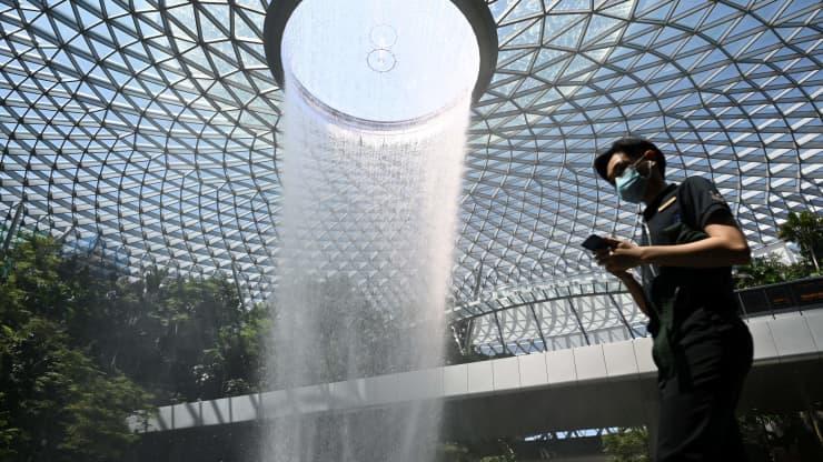 Một người đàn ông đeo khẩu trang che mặt đi qua thác nước trong nhà tại sân bay Jewel Changi, Singapore.