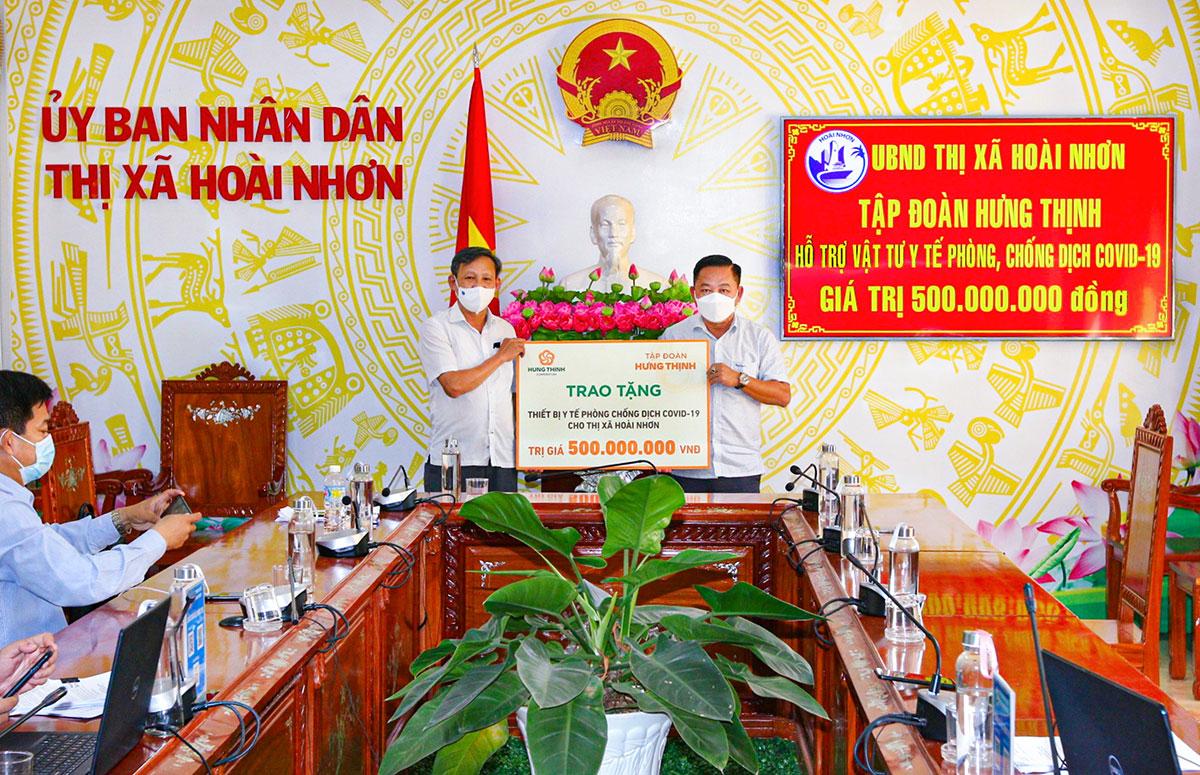 Ông Nguyễn Hữu Sang (bên phải) – Đại diện Tập đoàn Hưng Thịnh trao tặng các vật tư y tế trị giá 500 triệu đồng cho ông Phạm Trương – Bí thư Thị ủy, Chủ tịch UBND thị xã Hoài Nhơn vào chiều ngày 30/6/2021