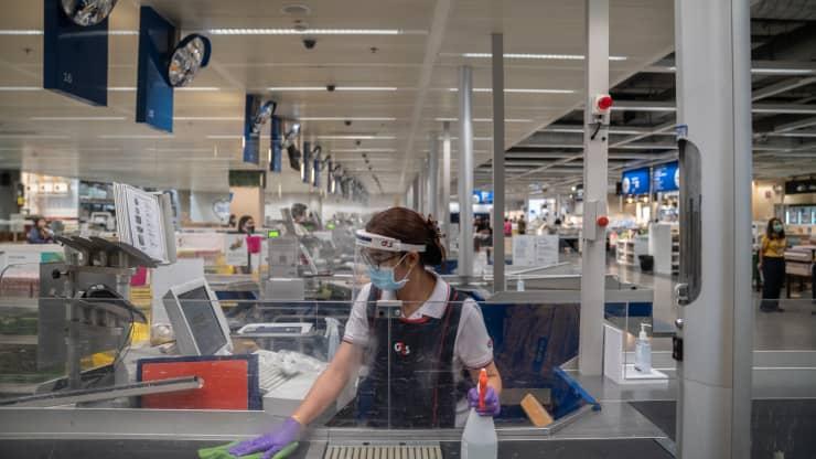 Một công nhân đeo khẩu trang bảo hộ, găng tay và khăn che mặt khử trùng quầy thanh toán bên trong cửa hàng Ikea.