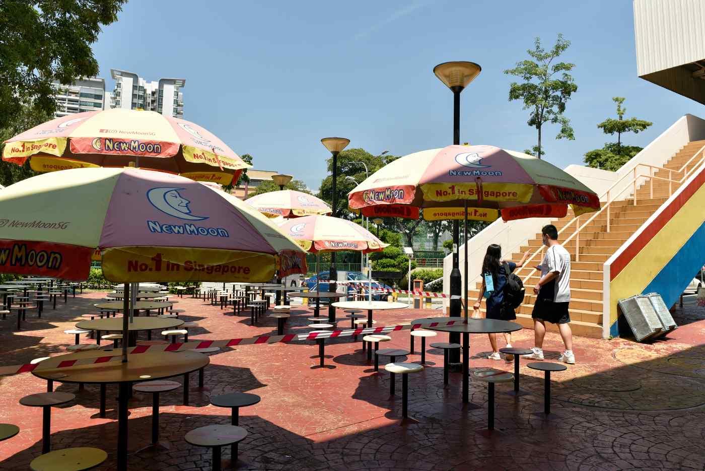 Mọi người đi ngang qua một khu ẩm thực vắng vẻ ở Singapore: Chính quyền thành phố gần đây đã thắt chặt các yêu cầu về cách xa xã hội sau khi bùng phát các trường hợp COVID-19. © Reuters