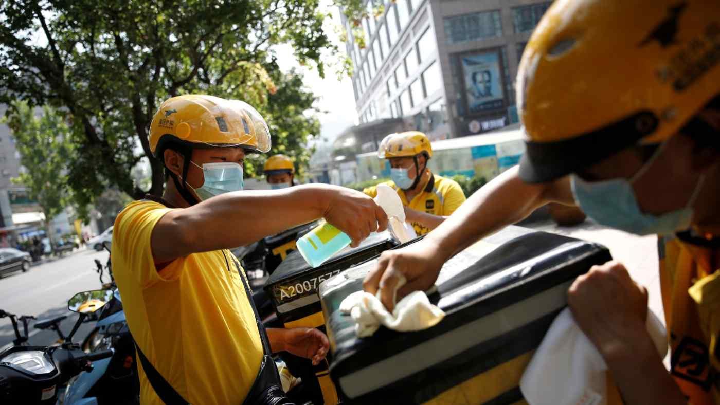 Nhân viên giao đồ ăn Meituan khử trùng xe tay ga và hộp giao hàng của họ trước khi họ bắt đầu công việc ở Bắc Kinh. © Reuters