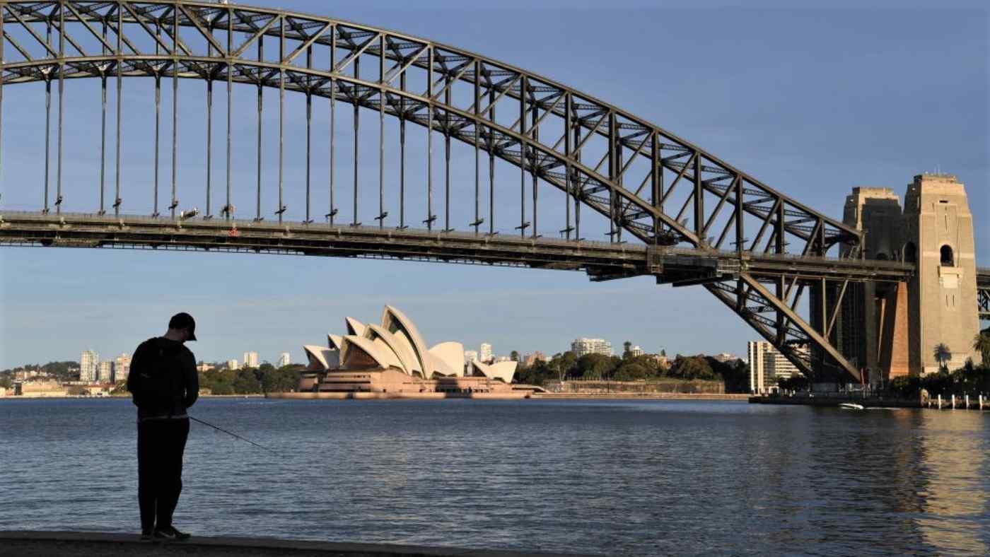 Một người đàn ông đánh cá qua bến cảng từ Nhà hát Opera Sydney vào ngày 27 tháng 7. Cư dân và các cơ sở kinh doanh ở khu vực Sydney rộng lớn hơn đang bị hạn chế chặt chẽ về COVID-19. © Hình ảnh Getty