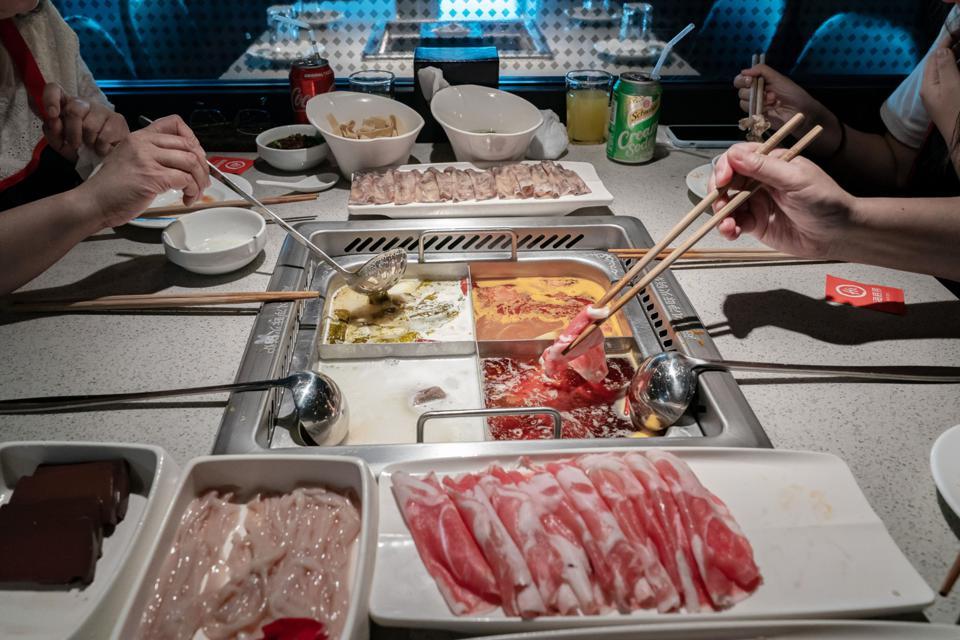 Đĩa thức ăn sống đặt trên bàn khi thực khách nấu chúng trong nồi tại một nhà hàng lẩu Haidilao ở Hồng Kông, Trung Quốc. © 2018 BLOOMBERG FINANCE LP
