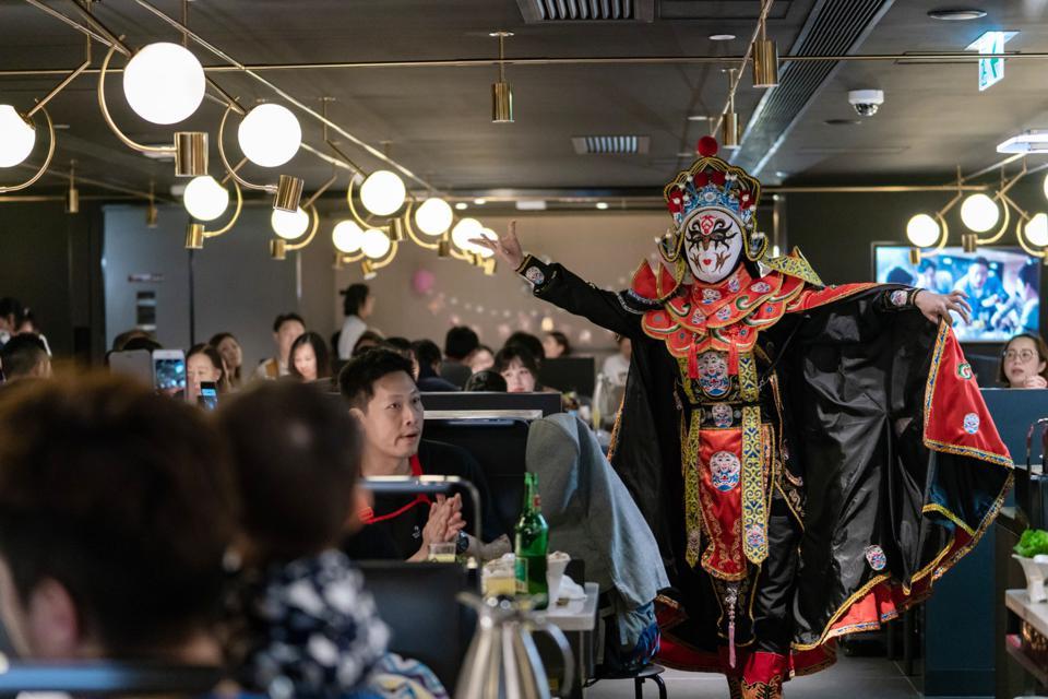 Một nghệ sĩ thay đổi khuôn mặt Trung Quốc biểu diễn tại một nhà hàng lẩu Haidilao ở Hong Kong, Trung Quốc. © 2018 BLOOMBERG FINANCE LP