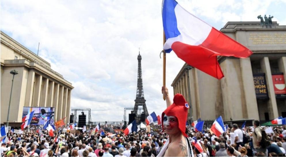 Một người biểu tình vẫy cờ tổ quốc trong cuộc phản đối tiêm chủng bắt buộc