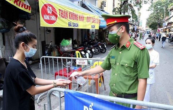Người dân vào mua đồ thiết yếu tại chợ Đồng Xuân được lực lượng chức năng yêu cầu rửa tay sát khuẩn