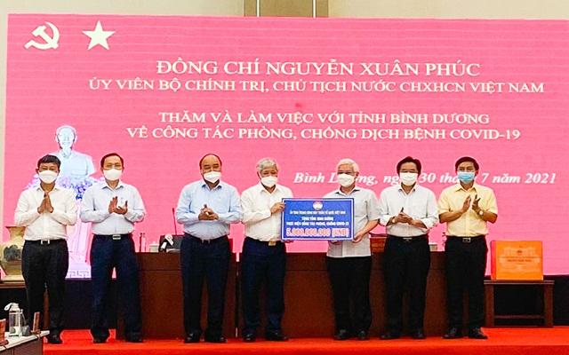 Chủ tịch nước Nguyễn Xuân Phúc trao bảng tượng trưng số tiền ủng hộ Bình Dương trong công tác phòng chống dịch.
