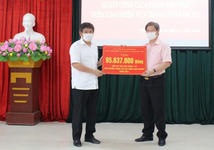 Bí thư Đảng ủy Khối các cơ quan tỉnh Phú Thọ trao tiền ủng hộ mua thẻ BHYT tặng cho hộ cận nghèo cho lãnh đạo BHXH tỉnh