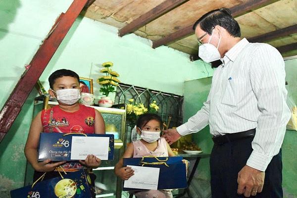 Chủ tịch UBND TP.HCM Phan Văn Mãi thăm hỏi, tặng quà 2 cháu N.H.K. và N.T.V. - Ảnh: VIỆT DŨNG/SGGP
